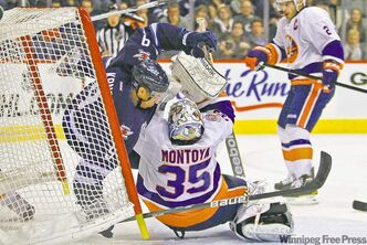 Winnipeg Jets forward Evander Kane crashes into New York Islanders goaltender Al Montoya during second period NHL action in Winnipeg Tuesday.