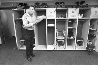 Retired Bombers defensive lineman Doug Brown notices that his name tag is missing from his locker in the team's dressing room Wednesday.
