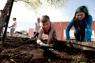 Liam and Shelby dig into their work, getting the school's garden beds ready for spring planting.