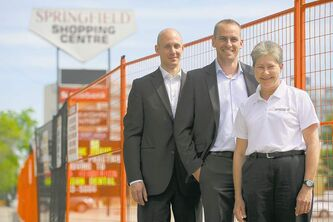 Michael Acht of MMP Architects (left), Frank Koch-Schulte, general manager of the Edison Rental Agency, and Miriam Bergen, president of Edison, stand in front of the strip mall that will be demolished to make way for the development rendered abvove.