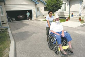 ALS sufferer Judy Patterson leaves for an afternoon walk with her support worker Colleen Hotricano, while her husband Ron watches from the garage.