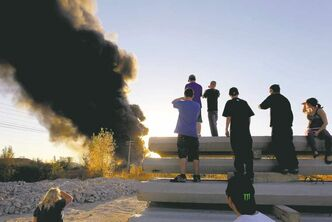 Onlookers watch as thick, black smoke billows into the sky on Monday from a fire at a St. Boniface fuel company.
