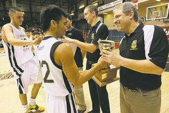 Gophers' Josh Magpantay hands the trophy to coach Phil Penner.
