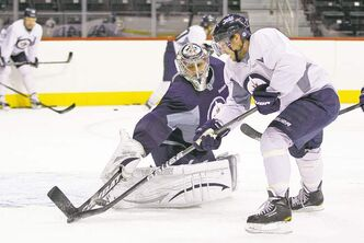 Winnipeg Jets goaltender Ondrej Pavelec shuts the door on a scoring attempt by forward Kyle Wellwood during day three of training camp at the MTS Iceplex Tuesday.