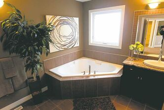 Ensuite features a triangular soaker tub, four-foot shower, brown tile floor and earth-tone palette.