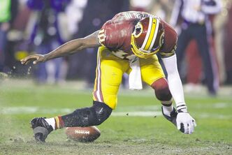 Washington Redskins quarterback Robert Griffin III twists his knee as he reaches for the ball after a low snap during an NFL wild-card playoff game against the Seattle Seahawks on Jan. 6. Griffin had his lateral collateral ligament repaired and his ACL reconstructed for a second time. The surgery was performed Jan. 9. Coach Mike Shanahan (above) has been criticized for not removing Griffin from the game earlier, especially when Griffin was limping noticeably.