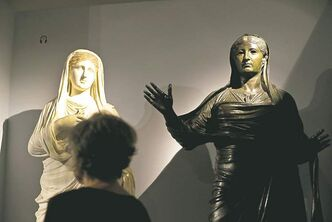 A woman looks at a statue of Empress Livia, right, found in the ruins of the ancient Roman town of Herculaneum.