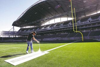 A worker places finishing touches on Investors Group Field May 7.