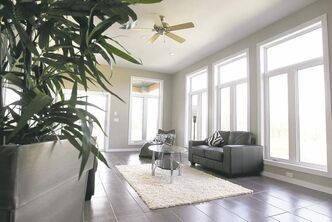 A sunroom off the family room features a three-part picture window on the rear wall.