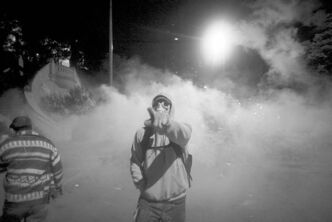 A protester in a gas mask emerges from a cloud of tear gas in Taksim Square Monday.