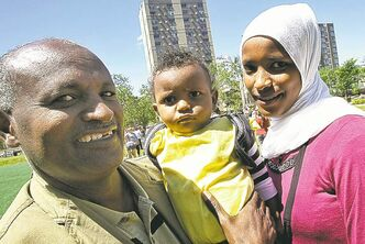 Kasim Kawo (left) with his daughter, Milki, 14 months, and wife Balkisa join a rally at Central Park to protest federal cuts to refugee health benefits.
