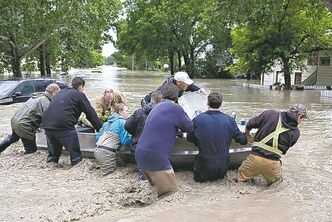 Residents and rescuers fight against the current in a flooded street in High River, Alta. on June 20, 2013 after the Highwood River overflowed its banks. THE CANADIAN PRESS/Jordan Verlage