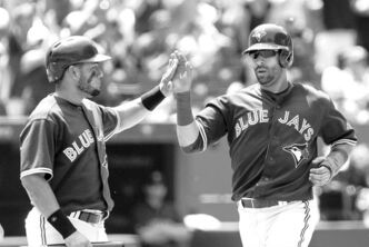 Toronto Blue Jays Jose Bautista (right) and Melky Cabrera celebrate scoring on an RBI double from Edwin Encarnacion.