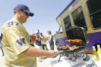 Greg Simes flips burgers next to the bus he and his friends use for tailgating at Bomber games.
