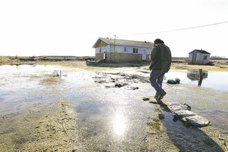 A Lake St. Martin resident steps on sandbags on the  flooded First Nation in 2012. Researchers say the reserve's new site is just as prone to flooding as its old one.