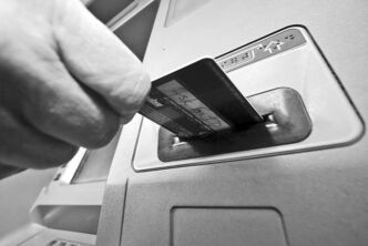In this Saturday, Jan. 5, 2013 photo, a person demonstrates using a credit card in an ATM machine in Pittsburgh. ricans stepped up borrowing in January to buy cars and attend school, while staying cautious about using their credit cards. (AP Photo/Gene J. Puskar)
