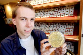 Christopher Porco, a 21-year-old coin expert with Gatewest Coin hefts an impressive one kilogram gold coin.