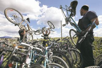 WRENCH executive director Pat Krawek (right), volunteer co-ordinator Robin Ellis (centre) and mechanical director Geoff Heath check out rows of stacked bikes. Below, a worker checks out a bike's mechanics.