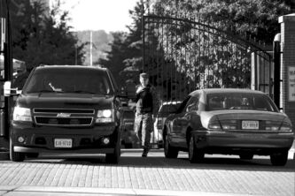 A U.S. navy member checks vehicles at the Washington Navy Yard entrance Wednesday, two days after a shooter killed 12 people in one of the buildings.