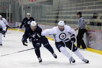 Winnipeg Jets forward Blake Wheeler fends off defenceman Zach Redmond during a September 2013 practice at the MTS IcePlex.