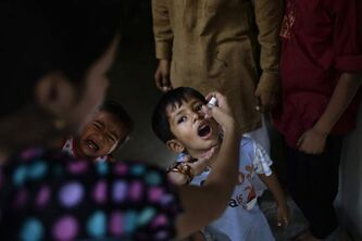Pakistani health worker Naela Emanuel, 18, left, gives a polio vaccine to child in a Christian neighborhood in Islamabad, Pakistan last year.