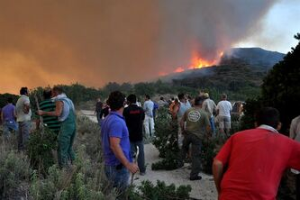 In this Sunday, Aug. 19, 2012 photo local residents and firefighting volunteers are seen holding makeshift fire beaters as a large forest blaze looms on the Greek eastern Aegean Sea island of Chios. Hundreds of firefighters, soldiers and volunteers were struggling for a third day Monday to tame a massive fire that burnt some 7,000 hectares of forest, cultivated land and groves of the island's famed mastic trees. Smoke from the blaze, which was swept on by gale-force winds, was carried as far as the southern island of Crete, more than 350 kilometers (230 miles) away. (AP Photo/Icon Press) GREECE OUT