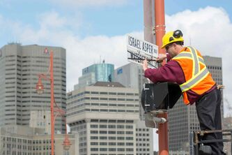 City of Winnipeg worker Kris Gustowski changes the street sign of Waterfront Drive to Israel Asper Way in front of the Canadian Museum for Human Rights Monday morning.