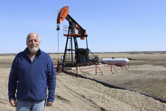 George Wady stands in front of an oil well in the new Birdtail Field near Birtle. He shares mineral rights with two other people, including a woman in California he's never met.