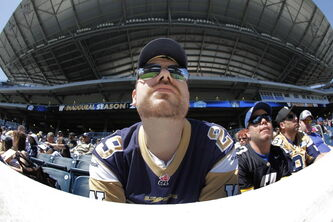 Season ticket-holder Kevin Carlson checks out his team, the Winnipeg Blue Bombers, and the new Investors Group Field during opening day of training camp in Winnipeg Sunday.
