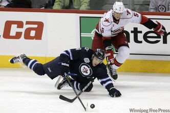 Winnipeg Jets' Jason Jaffray (41) tries to keep control of the puck after getting checked by Carolina Hurricanes Bryan Allen (5) in the third period.