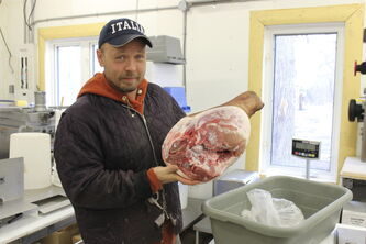 Clint Cavers holds up a ham leg in the Harborside Farms meat shop