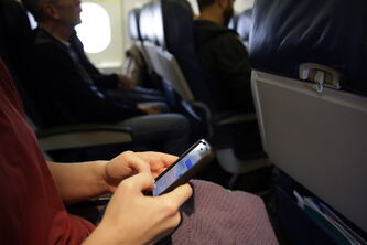 A passenger uses a cellphone in an airplane cabin prior to a flight.