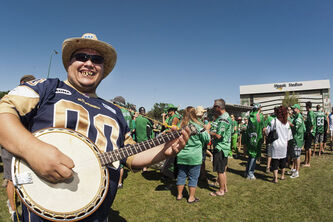A Bomber fan plays a banjo before CFL football action between the Saskatchewan Roughriders and the Winnipeg Blue Bombers in Regina, Sask., Sunday.