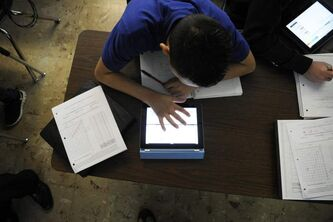Grant Beacon Middle School student, Jeriah Garcia, 13-years-old, works out an algebra problem on his school-supplied iPad in class at Grant, Colo. on Jan. 17, 2012.