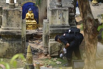 An Indian National Security Guard soldier collects the evidence from the site a blast at the Mahabodhi Temple or the great Awakening Temple complex, in Bodhgaya, about 130 kilometers (80 miles) south of Patna, the capital of the eastern Indian state of Bihar, Monday, July 8, 2013. A series of blasts hit three Buddhist sites in eastern India early Sunday, injuring at least two people. The temple is a UNESCO world heritage site where Buddha is said to have attained enlightenment. (AP Photo/Manish Bhandari)