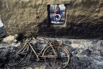 FILE - In this May 16, 2010 file photo, Indian villager Kabita Sahoo sits inside her house, burnt during violence between anti-Posco activists and police at Balitutha village in the eastern Indian state of Orissa. South Korean steel giant Posco said Tuesday, July 16, 2013, it has pulled out of a proposed $5.3 billion steel plant in southern India due to delays in acquiring land for the project. However, the company says it will go ahead with a separate $12 billion steel plant in eastern Orissa state. (AP Photo/Biswaranjan Rout, File)