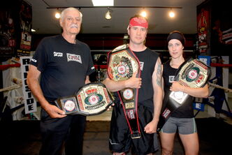 "Coach Dejan ""Pappa"" Paunovic, Kent Brown, and Patricia Girardin of Winnipeg Elite Boxing and MMA Academy show off the three belts the gym's fighters won at the 13th annual Ringside World Championships in Independence, Mo. earlier this month."