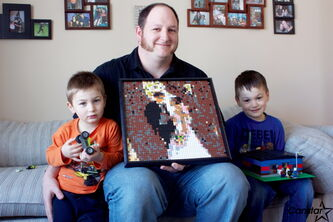Kevin Lariviere (centre) shows off the LEGO wedding picture he made of him and his wife as sons Liam and Caleb show off their creations.