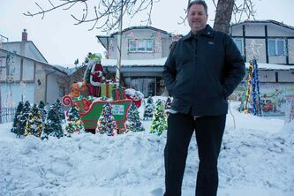 Michael Geiger-Wolf is shown with his Christmas light display outside his North Kildonan home.