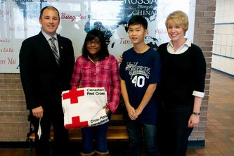 Salisbury Morse Place School Grade 7 students Sarah Mohammed Vincent Tran (centre) and teacher Leanne Smith (right) hand over a $2000 donation to Canadian Red Cross provincial director Shawn Feely (left). The money will go toward relief efforts in the Philippines.