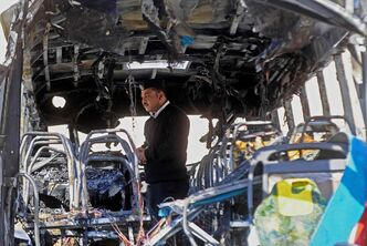 An Egyptian policeman inspects a damaged bus after a deadly explosion Sunday near the Egyptian border crossing with Israel in Taba, Egypt, Monday, Feb. 17, 2014. An explosion tore through a bus filled with South Korean sightseers in the Sinai Peninsula on Sunday, killing at least four people and raising fears that Islamic militants have renewed a bloody campaign to wreck Egypt's tourism industry.