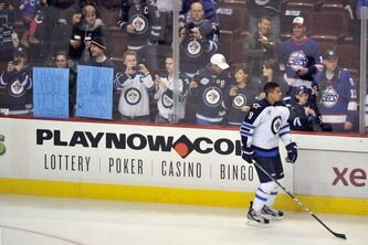 Winnipeg Jets' Evander Kane skates by supporters with signs and jerseys during warm-up before playing the Vancouver Canucks in Vancouver on Thursday. This is the Jets' first game in Vancouver since 1996.