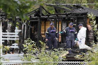 Investigators inspect the charred remains of the Winnipeg Beach home in which two young women died in Sunday's fire.