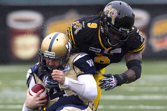 Winnipeg Blue Bombers starting quarterback Buck Pierce (left) is tackled by Hamilton Tiger Cats Renauld Williams (right) during first half CFL action in Hamilton on Saturday.