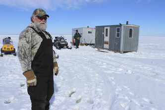 Cyril Lillies stands in front of fishing shacks in the middle of Shoal Lakes.