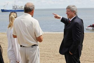 Prime Minister Stephen Harper points to a research ship as he talks to Lake Winnipeg researcher Dr Al Kristofferson (left) on Gimli Beach last week.  Harper announced today $18 million in funding to clean up Lake Winnipeg.