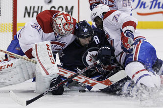 Montreal  goaltender Carey Price and blue-liner P.K. Subban try to keep the loose puck from Winnipeg's Bryan Little (18) during second-period action before the Jets' Blake Wheeler tapped the loose puck in for a goal.