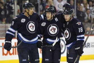 Winnipeg Jets' Evander Kane, Toby Enstrom (centre), and Bryan Little celebrate a goal.