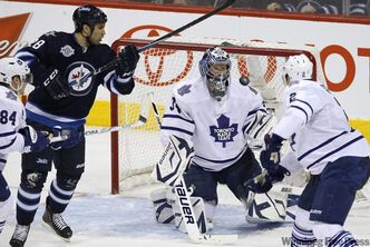 Patrice Cormier takes a whack at the puck in front of the Toronto Maple Leafs goal during a game on Dec. 31 in Winnipeg.