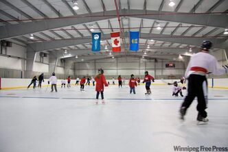 Local youth enjoy the opening day of the new rink in Fort Chipewyan, Alta. on Dec. 2, 2010. It is the first NHL-sized rink in North America to have a plastic surface.